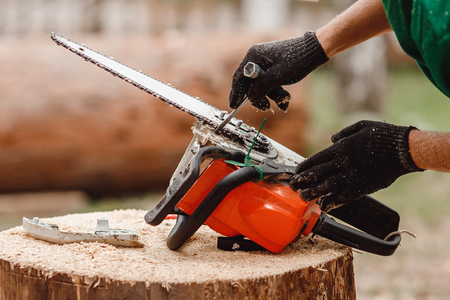 Woodcutter man repairs chainsaw, sharpens chain in forest