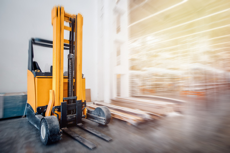 Warehouse industrial premises for storing materials and wood, there is forklift containers. Concept logistics, transport. Motion blur effect. Bright sunlight. Imagens