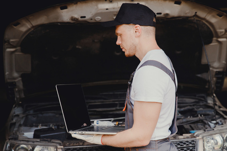Professional car mechanic using electrnoic diagnostic equipment laptop in auto repair service.