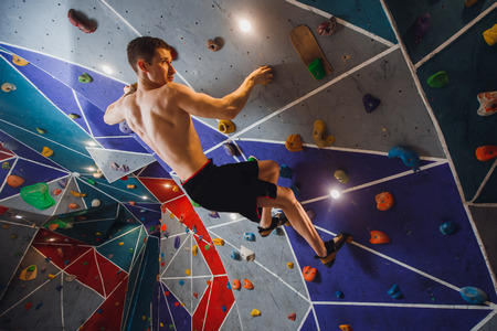 Close-up of male climber on sport climbing gym wall holding onto ledges. Stock Photo