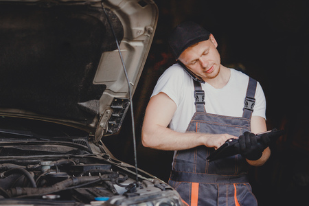 Professional car mechanic Calls on phone to client in auto repair service. Stock Photo