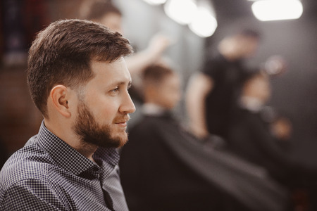 Barber shop Man in chair expects hairdresser styling Stock Photo