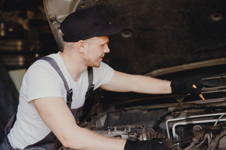 Car mechanic working diagnostic equipment at automotive service