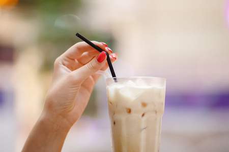 Cold coffee with ice in woman hand, blurred background. Stock Photo - 107413750
