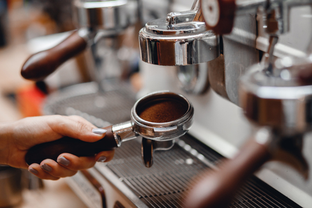 Young barista woman is preparing coffee machine for making espresso. Tamper Filter holder Stock Photo - 107413758