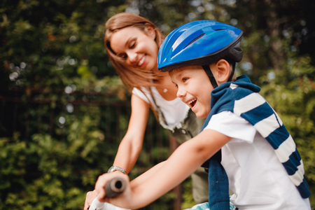 Sister and little brother learning to ride bicycle park having fun together Stock Photo