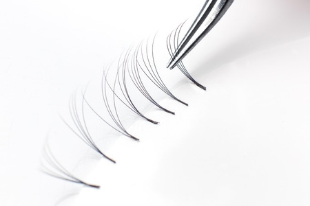 Master of eyelash extensions works with tweezers, forms bundle from pallet Stock Photo - 107413801