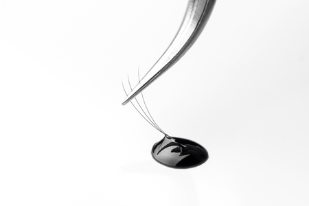 Master of eyelash extensions works with tweezers, forms bundle from pallet Stock Photo - 107413806