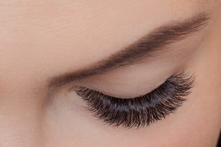 Concept eyelash extension procedure. Woman with long lashes in beauty salon. Top view Imagens
