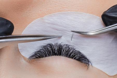 Eyelash extension procedure. Woman master making long lash with tweezers Stock Photo - 107413732