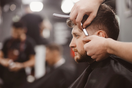 Man in barber chair, hairdresser styling his hair razor