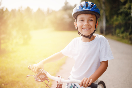 Little boy in helmet learning to ride bicycle park having fun Stock Photo