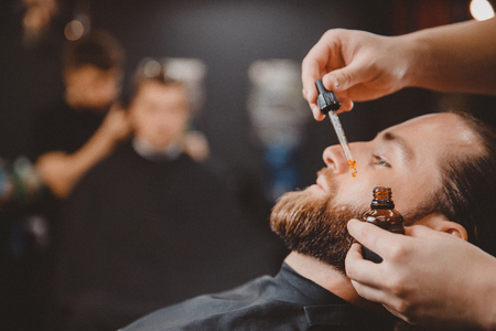 Barber applies beard oil with dropper for man in barbarshop.