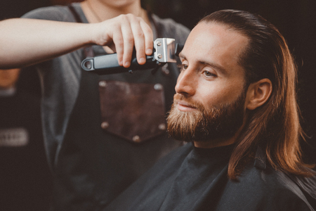 Hairdresser for men barber shop. Process of cutting long hair.