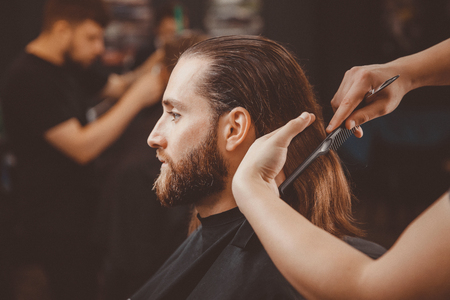 Barber shop. Man in barbershop chair, hairdresser styling his hair Stock Photo