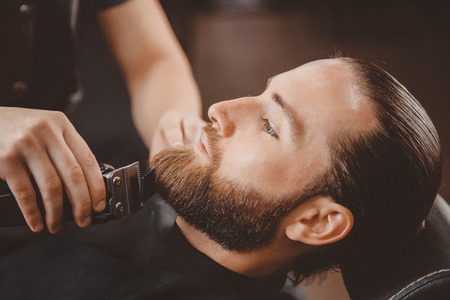 Man hipster having barber shave barbershop hair machine.