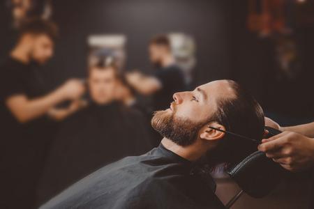 Barber shop. Man in barbershop chair, hairdresser styling his hair Standard-Bild