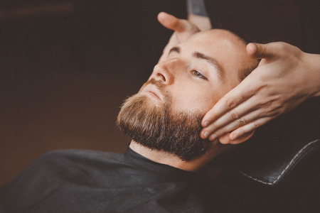 Barber uses oil massage to grow and strengthen beard to man.