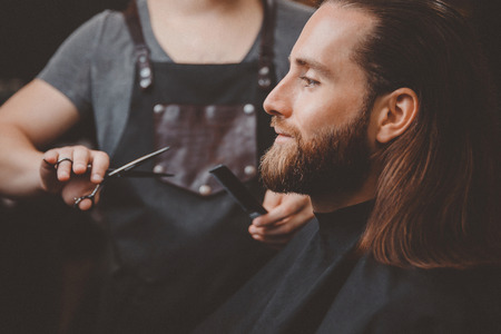 Man with beard and mustache, long hair sitting armchair in hairdresser, background barber. Stock Photo