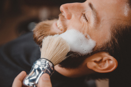 Hipster client man visiting in barber shop shaving beard