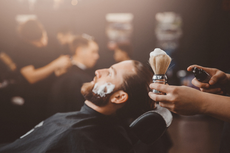 Barber process shaving razor bearded hipster man in barbershop.