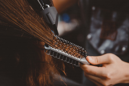 Close-up of drying long hair with hairdryer and comb