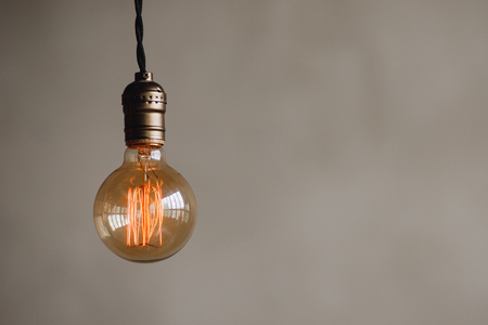 edison retro lamp on loft gray concrete background. Concept idea Stock Photo