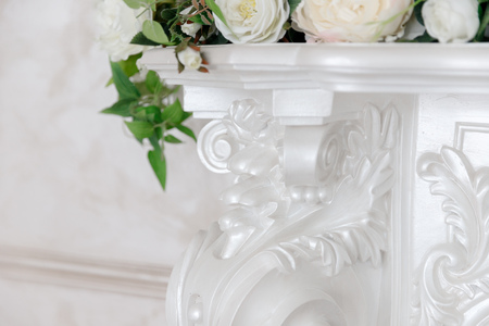 White fireplace in classic style with a forged black grill, decorated with flowers.
