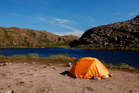 Orange tent overlooking mountain lake in fjord. Concept travel Norway.