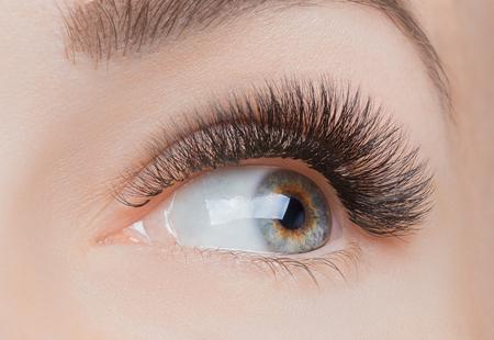 Macro photo woman with long lashes in beauty salon. Concept eyelash extension procedure. Standard-Bild