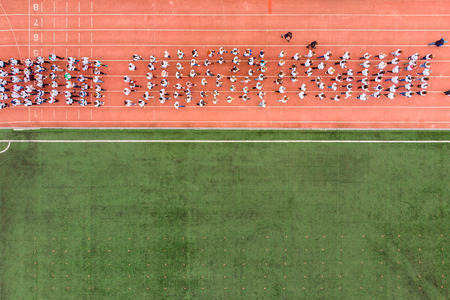 Top view drone of crowd of people on sports stadium football green lawn. Stock Photo