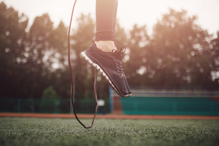 Male athlete performs exercise jump on rope in stadium sport workout.