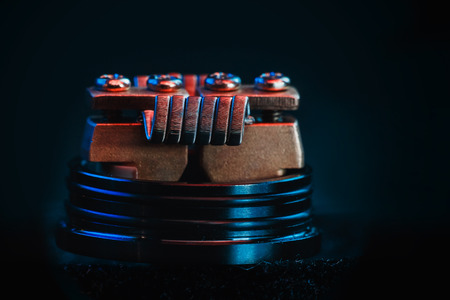 Winding close-up for electronic cigarettes from nichrome, fecral. vape. Staggerton Fused Clapton Coil on Dripper for vaping. Stock Photo