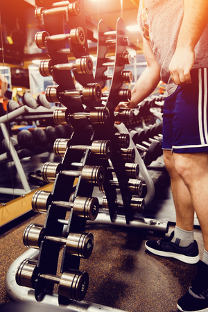 Sports equipment dumbbell rests in a row. man takes a dumbbell. high contrast and monochrome color tone. Stock Photo