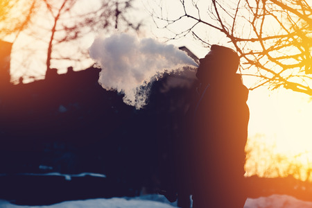 man is vape steam smoking an e-cigarette on the sunset. high contrast and monochrome color tone. Stock Photo