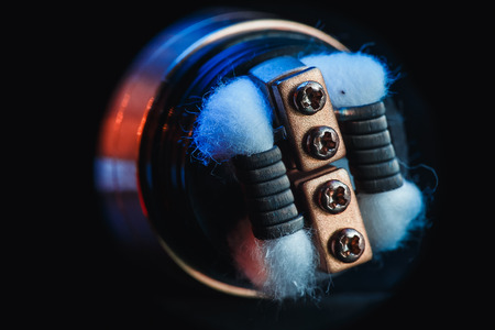 Close-up of cotton wool, coil and electronic cigarette vape on a black wood background. vaping device