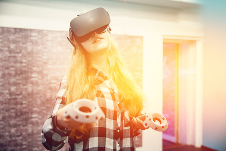 Blonde girl in glasses and mask for VR. Smiling and laughing. With sunlight and toning. concept of virtual reality.high contrast Stock Photo