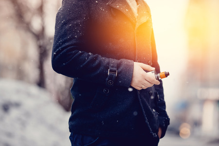 Man holds in his hand an electronic cigarette vape type mod. He is wearing a coat. Winter. Concept of steam without smoke and tobacco. Toning and highlighting.vaping