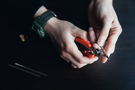 male master installs a coyle. Spiral for electronic evaporator and cigarette. Vape, vaping. Pliers, wire, fichral, coil, screwdriver Stock Photo