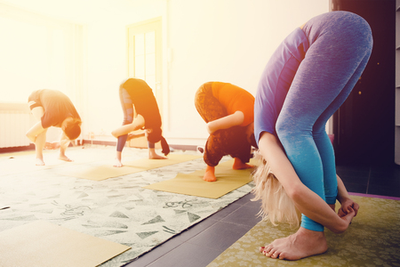 Fitness trainer shows exercises from yoga and stretching for a group of friends. Concept of team health and training posture.