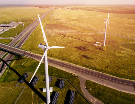Top VIEW of road passing near wind farms and solar panels in middle of green field. Concept clean energy eco-friendly. Stock Photo