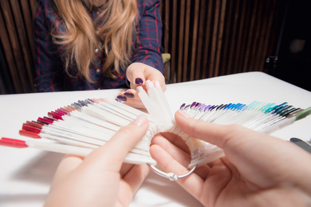 Master of manicure nude nail polish offers palette colors to girl in purple shirt with long blonde hair Stock Photo