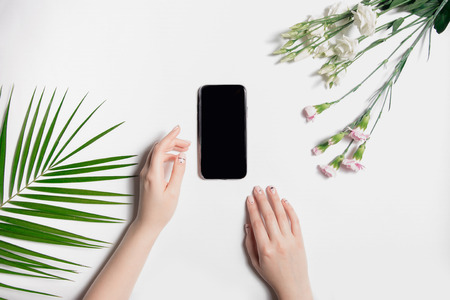 Beautiful well-groomed womans hands with neat light manicure lie on table near Phone. Fashionable green palm leaf, delicate pink and white flowers. Top view