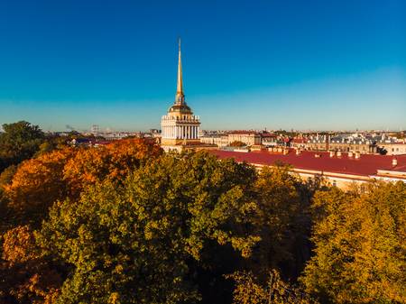 Golden spire Admiralty of St. Petersburg shines against background Sunny blue sky, red roofs and autumn yellowing leaves trees