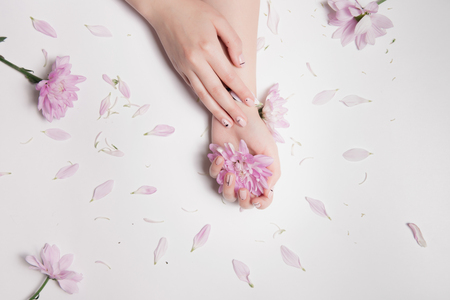 Fashion composition. One female hand with beautiful light manicure lies other, which is pink flower bud, and petals are neatly scattered on table.