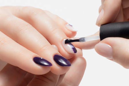 Beautiful well-groomed womans hands. Process of applying decorative nail Polish purple