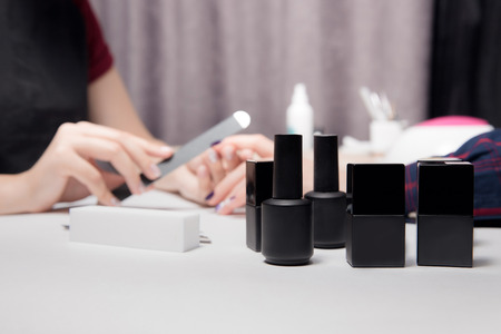 Close-up black jars, bottles, containers of nail polish. Process creating manicure beautiful female hands in background