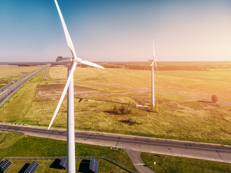 wind turbine close-up on background of forest belt and intersecting roads. Concept of clean energy. Stock Photo