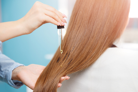 Master hairdresser applies oil to hair care for and restore growth of cuticles woman. Spa concept recovery. Banco de Imagens