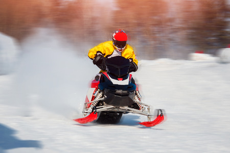 Snowmobile races jump in snow. Concept winter sports.